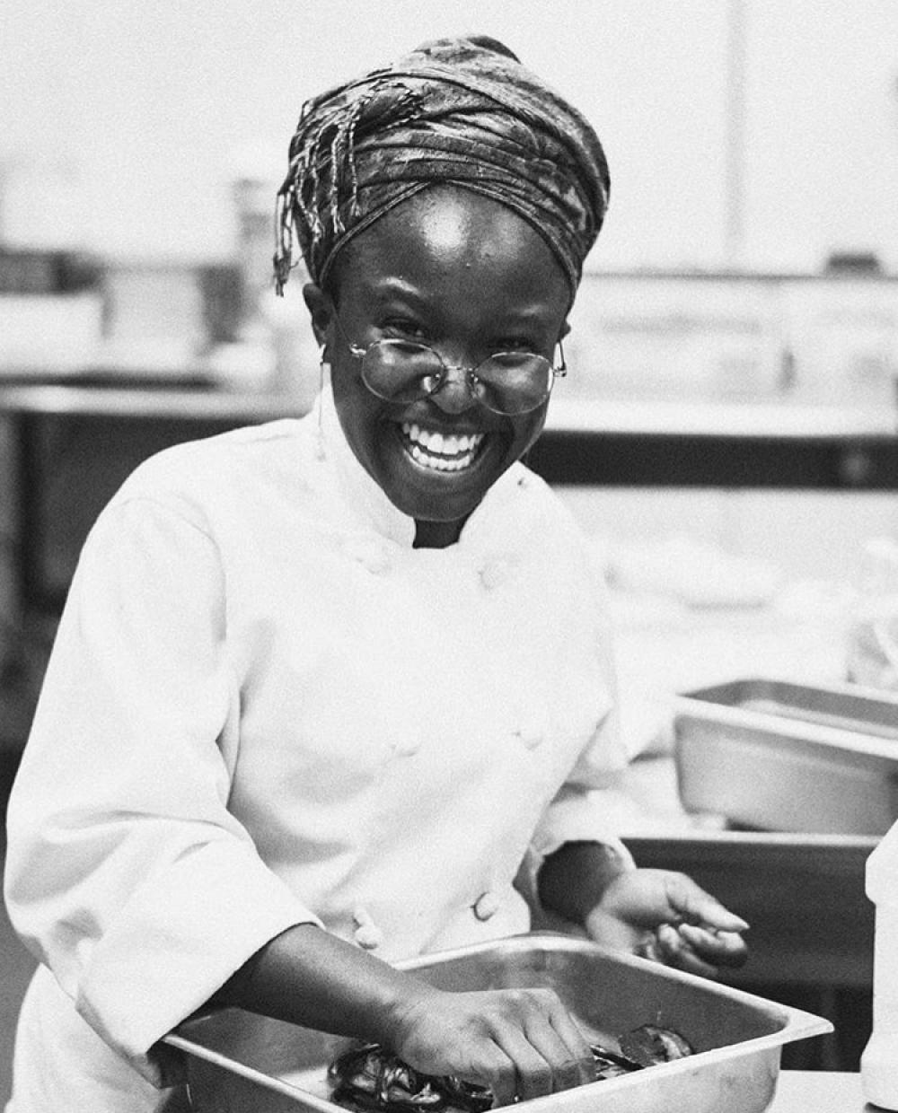 black and white portrait of smiling Black woman in chef's coat