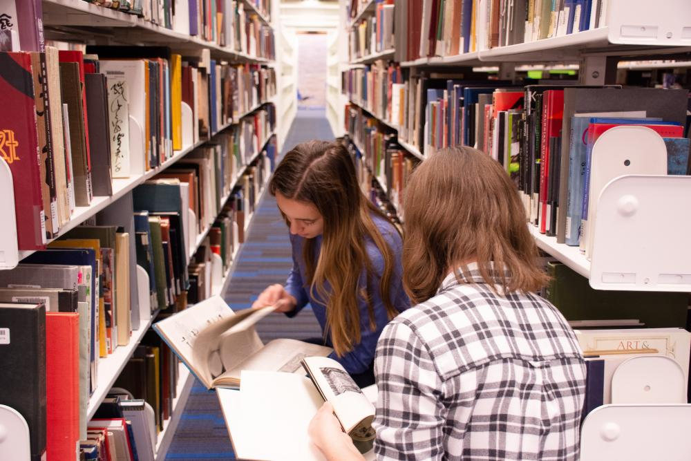 two female students flipping through books in a library