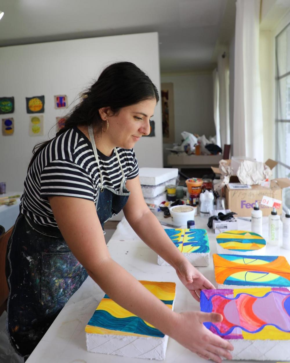 Print Studio Art Professor at The University of Texas at Austin Beverly Acha in Miami at the Fountainhead residency arranging her painting and print work in front of a window facing toward the right