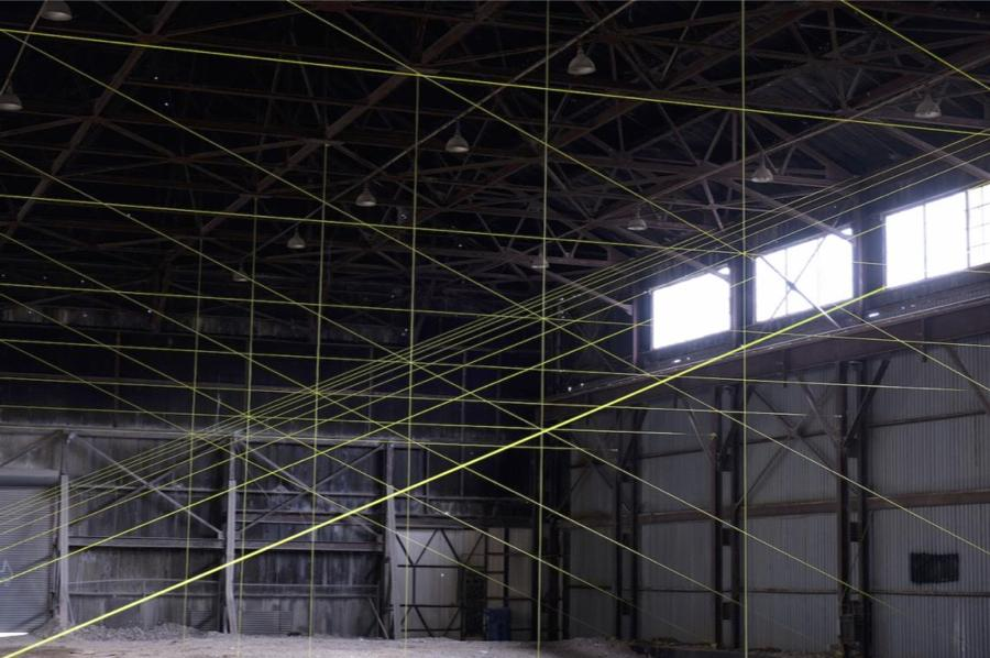 The inside of a large grey warehouse with two windows and neon yellow rope creating lines all over