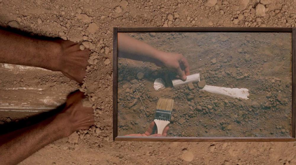 Image of hands excavating through and pushing at brown soil