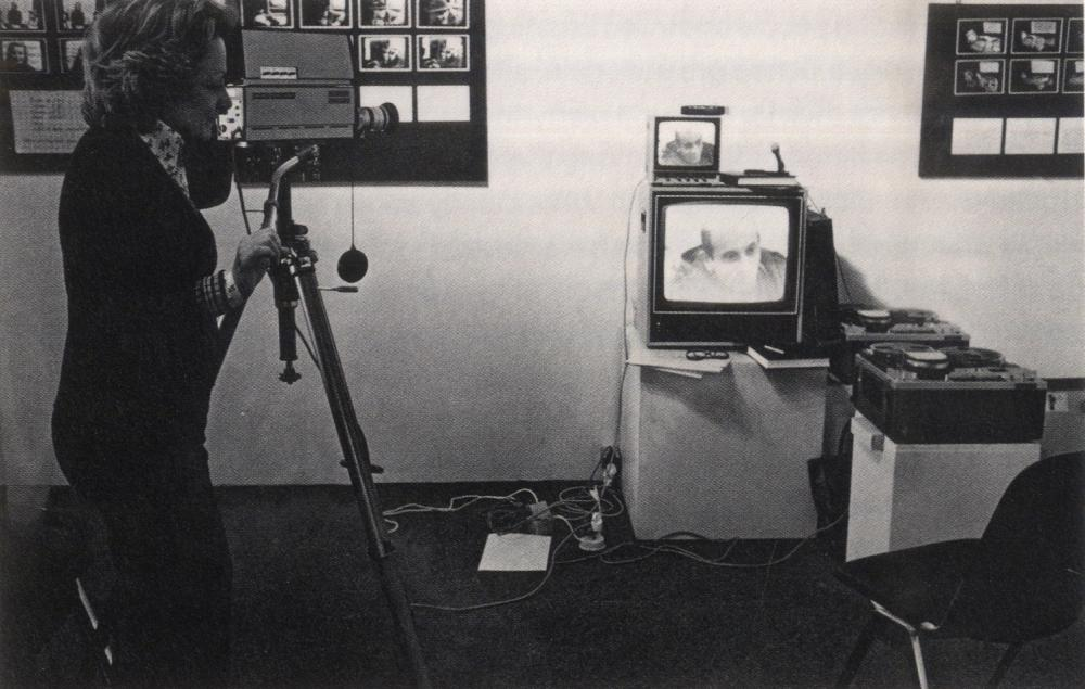 older photographic image of woman on the left using video camera and tv set