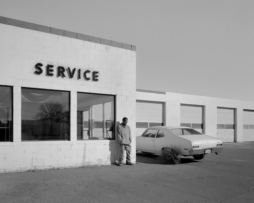Black and white photograph of a man leaning against a service station wall taken by photographer Bryan Schutmaat