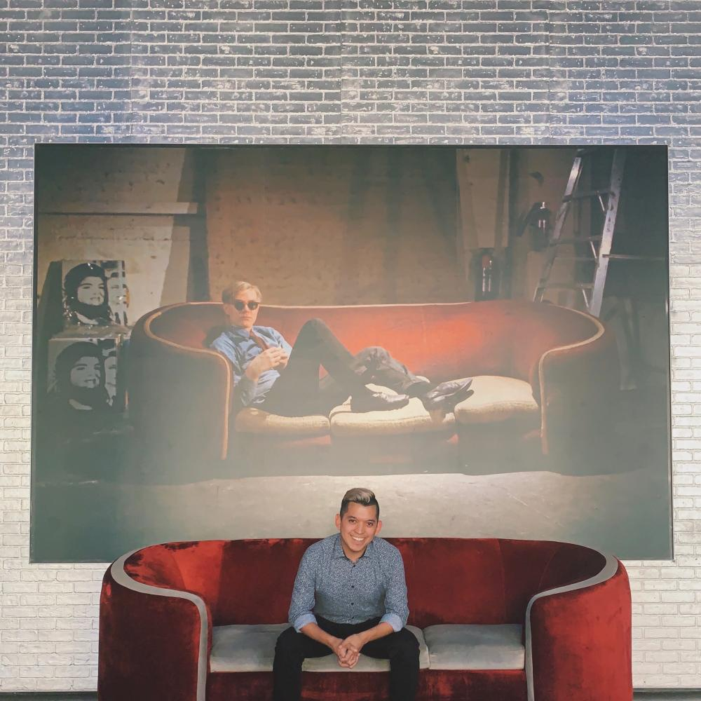 image of undergraduate in Art History Carlos Moreno in front of iconic wall at the Warhol Museum in Pittsburgh