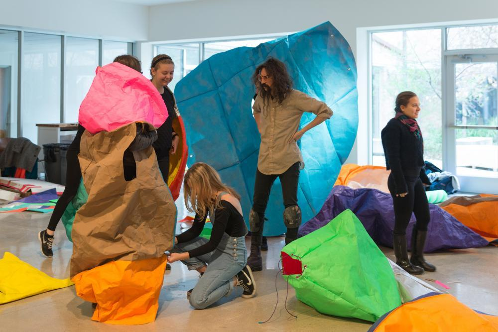 people interacting with colorful paper sacks