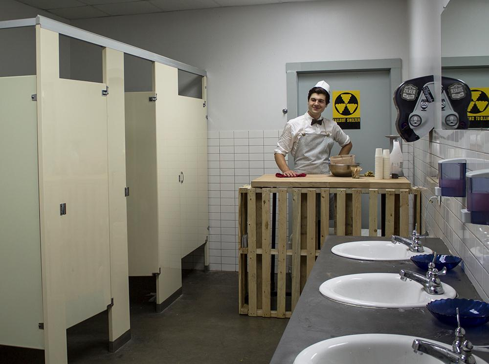 a man standing in a bathroom wearing a shop keeper's uniform