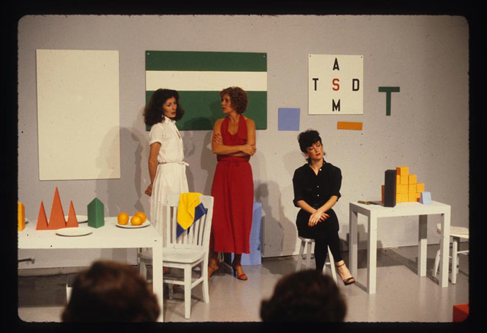 3 women on a stage surrounded by colorful, geometric objects and artworks on the wall, with audience members in foreground