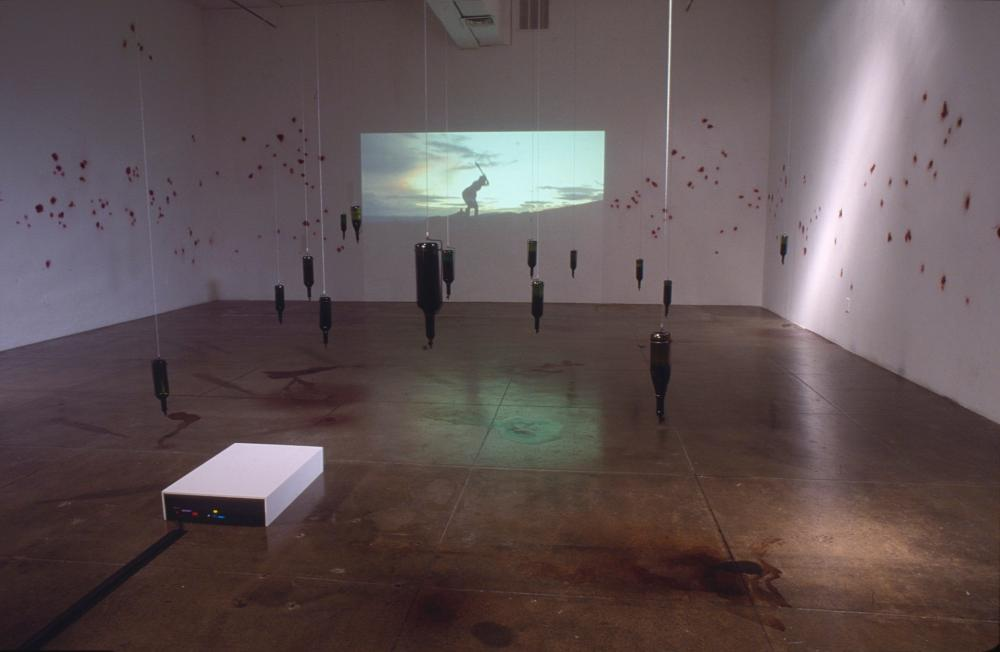 installation view of room whose walls are pockmarked and where wine bottles hang