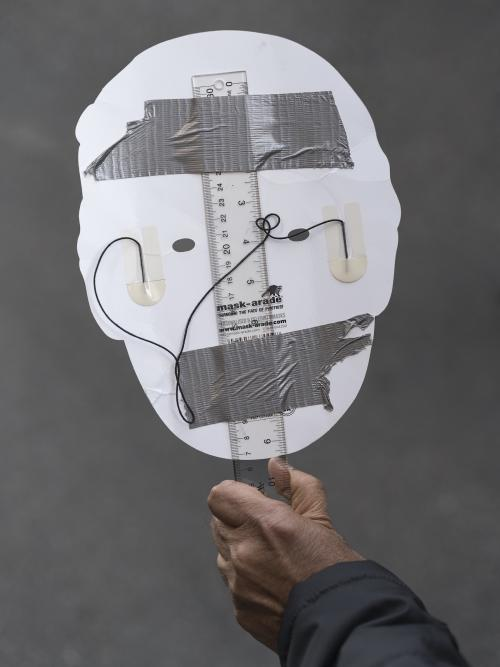 white outline of a head placed on a ruler with some wire