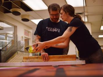 two printmakers working together on neon large scale print installation
