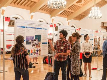 image of poster session with male student discussing research and poster with female audience