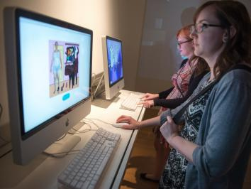 two students working on exhibition involving desktop computers