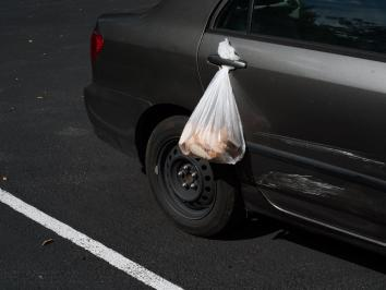photograph of a bag of bread being suspended in a car door