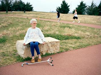 old woman sitting on park bench