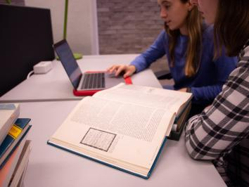 two women in library consulting a book in front of a laptop