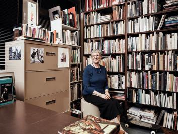 linda henderson seated in front of her bookcase within her faculty office