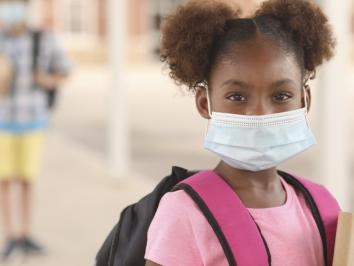 K-12 student in pigtails with mask during age of COVID-19 illustrating story about educating during pandemic from University of Texas at Austin graduate student candidate Cole Godvin