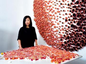 UT Austin Professor Beili Liu in front of an installation of her work to her right and a display of her materials on a table in front of her