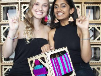 two women students holding up weaving project and their hands in a hook em gesture