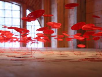 Beili Liu at the Crow Museum of Art in Dallas with an installation of hundreds of hand crafted threaded works suspended from the ceiling