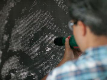 Image of UT Austin alumnus in Printmaking Miguel Aragon at work on large scale piece burning out holes in a print and seen from behind