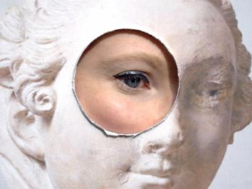 film still of an eye looking through a circular hole cut out of a board depicting marble sculpture on its face