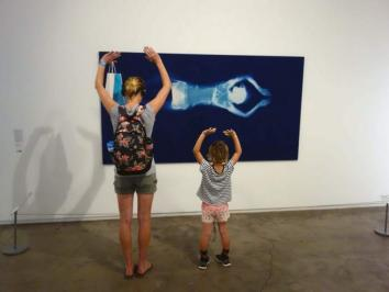 two gallery viewers backs and their arms are raised
