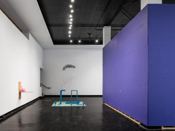 Installation with purple and white walls surrounding a freestanding object