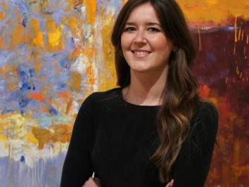 portrait of a woman with long brown hair in front of an abstract canvas painting