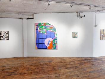an open gallery space with white walls and brown wooden floors. there are paintings hanging on the walls, each in different styles and multiple, bright colors