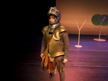 man standing in suit of armor on stage