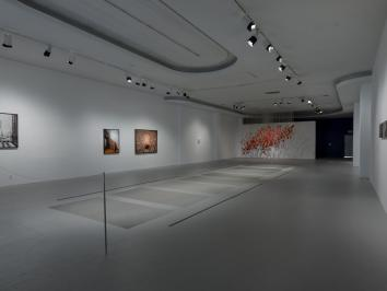 image of long exhibition hallway with multiple sculptures strewn about