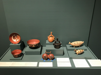 three images of andean ceramics being installed into a museum with the help of preparatory and curators