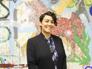 image of woman in black blazer in front of latino artist mural