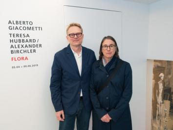 two artists standing in front of title text for exhibition on wall behind them