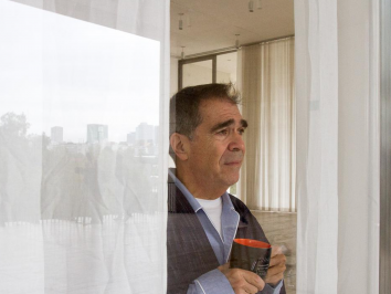 man staring out of hotel window