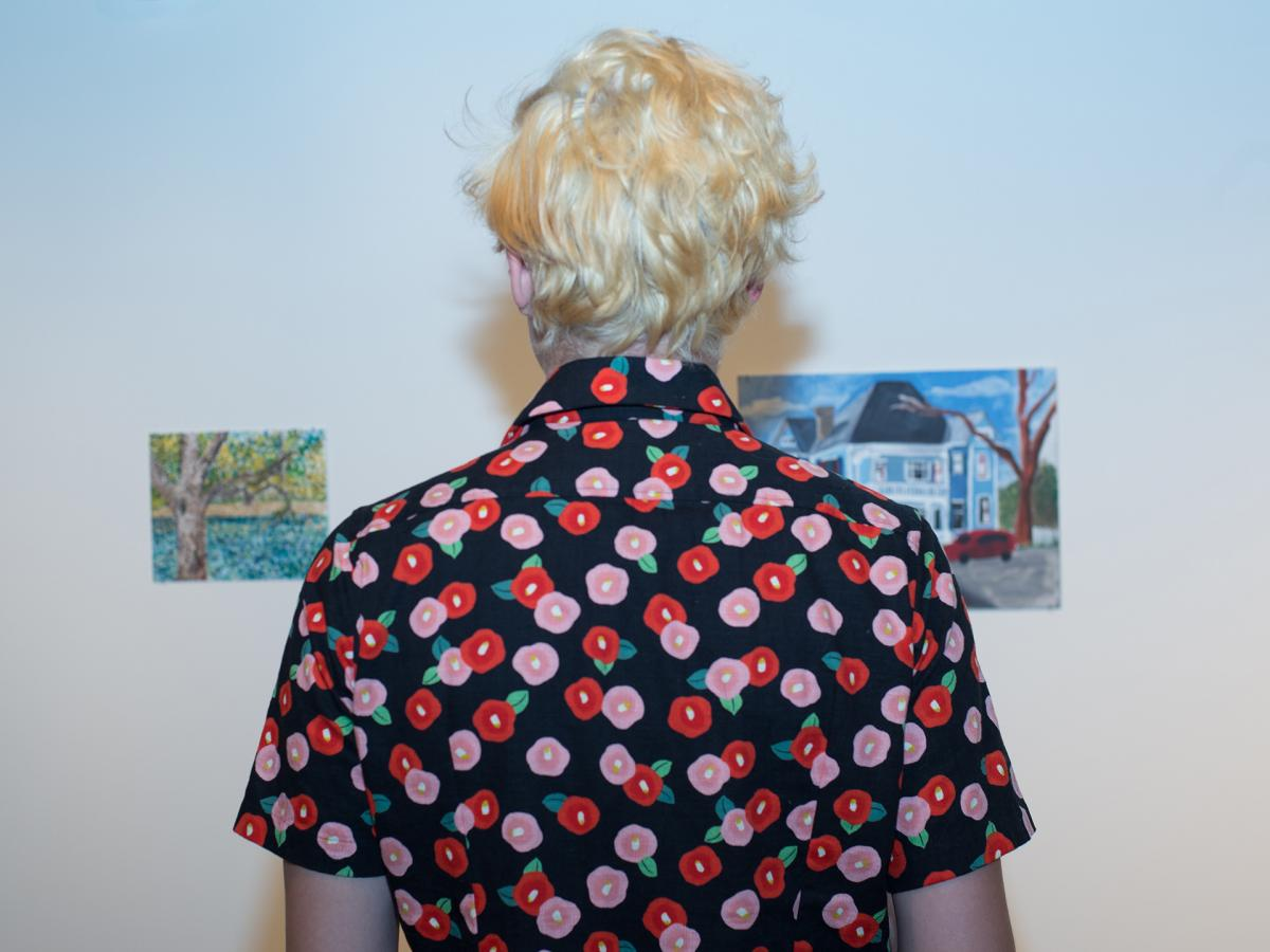 student with back to camera looking at art