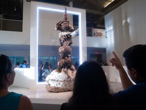 students in the foreground looking at stacked burl installation in background
