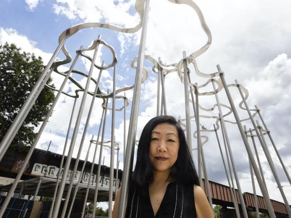 Artist and Studio Art faculty member Beili Liu in front of downtown Austin sculpture Cloud Pavilion