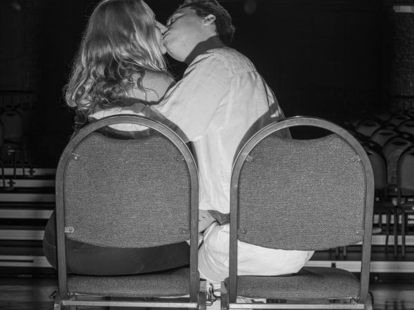 black and white photo of a pair kissing while seated with the chair backs turned toward the camera