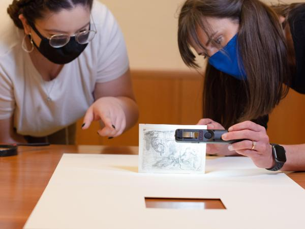UT Austin undergraduate Art History major Natalie Ponder looking at print archive collection piece with curator Holly Borham