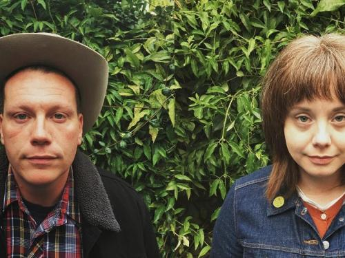 portrait of two artist in front of a garden hedge