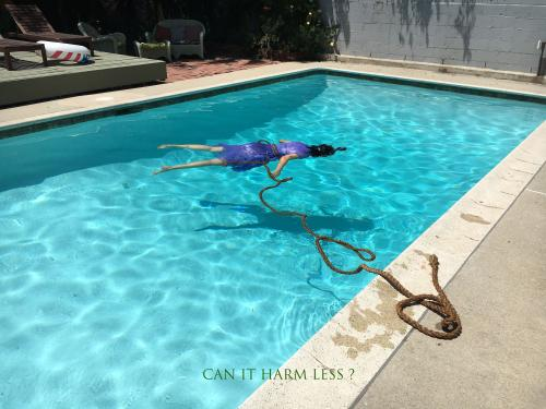 woman in purple dress floating in pool face down with rope spooling from waist to poolside