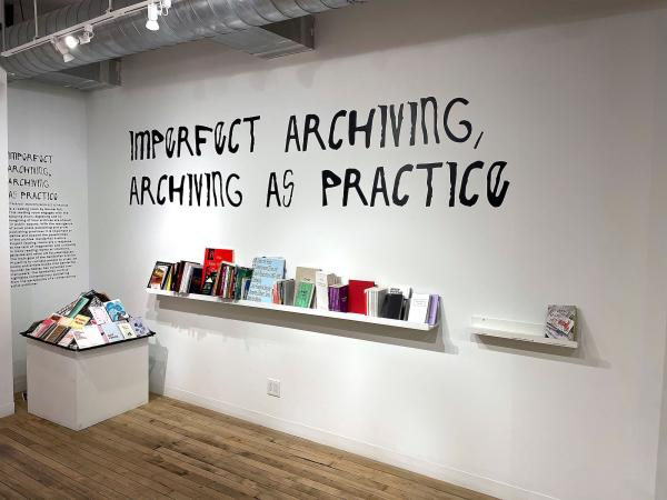 printed materials placed in a gallery setting with black vinyl wall text reading Imperfect Archiving Archiving as Practice from artist and UT guest artist in print Be Oakley
