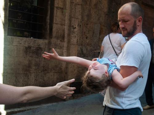 small child leaning back in a man's arms to reach another hand coming in from outside the frame