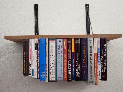 books on a bookshelf defying gravity by being upside down in a work by artist Rebecca Marino