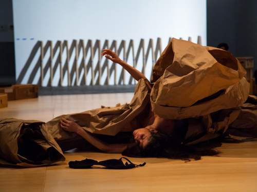image of an artist performing a piece under tarp of large brown paper