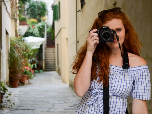 redheaded woman holding a camera up to one eye