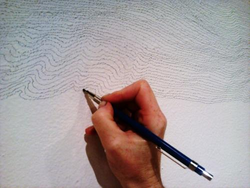 hand holding pencil drawing consecutive lines