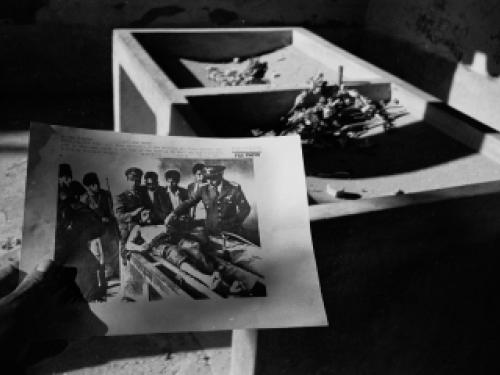 the photo is in black and white. a man is holding a photo of men in military uniforms gathered around a shirtless man in a stretcher. he seems hurt or sick.